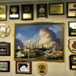 A wall of friendly plaques and recognitions surround a painting of Fort Worth, Texas in the Officers' mess.